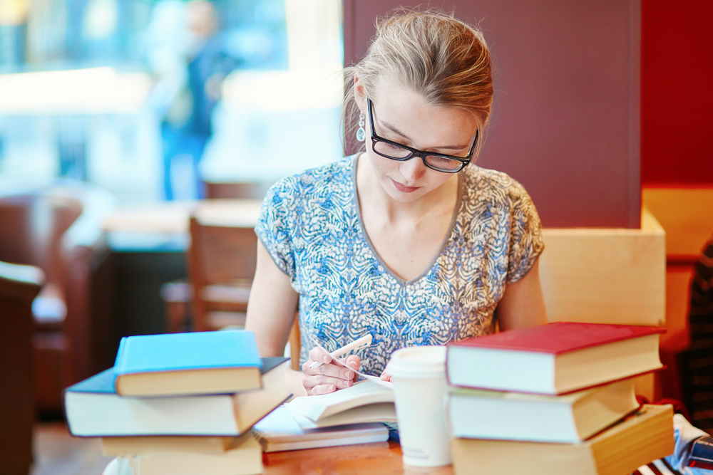 Young woman studying for test in coffeehouse with coffee and textbooks